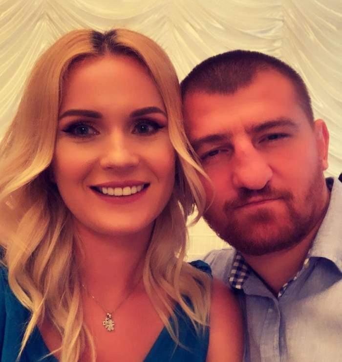 Cătălin Moroșanu și soția lui sunt la o petrecere. El poartă cămașă bleu, iar ea rochie albastră și zâmbește.