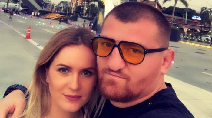 Cătălin Moroșanu și soția lui, Georgiana, pe aeroport. Ea zâmbește slab, iar el poartă tricou negru și ochelari de soare.