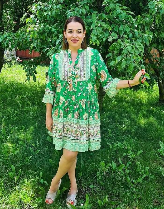 Oana Roman e în grădină, poartă rochie verde cu imprimeu colorat și zâmbește. În spatele ei sunt copaci.