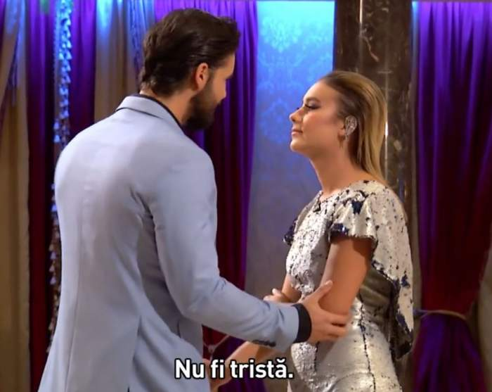 Momentul în care Andi Constantin a eliminat-o pe Alexandra de la Burlacul. Vedeta îi spune tinerei să nu fie tristă și îi ține mâna pe braț. Ea poartă rochie cu paiete argintii și el sacou bleu.