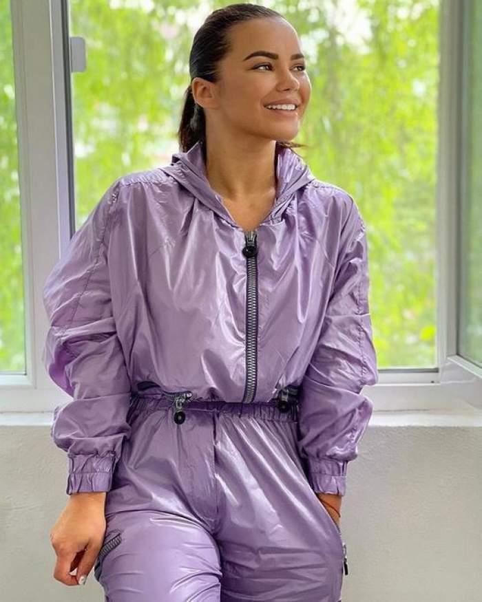 Carmen de la Sălciua e lângă un geam, zâmbește privind în sus și poartă trening mov.