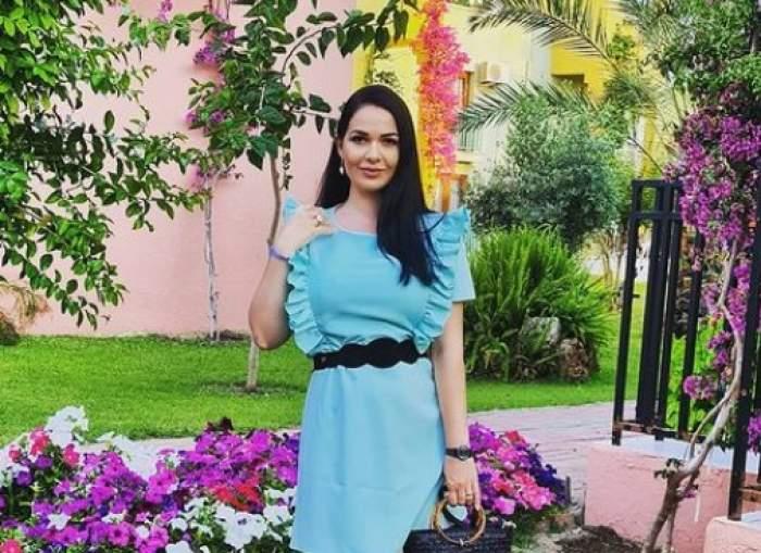 Deea Maxer într-o rochie albastră, în grădină