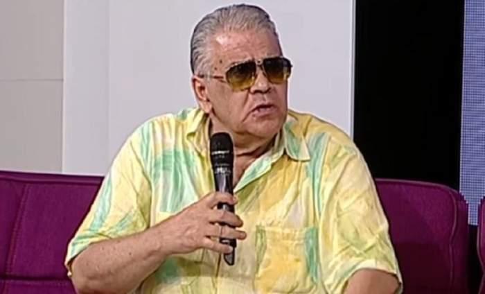 Florin Condurățeanu poartă ochelari de soare, vorbește la microfon și e îmbrăcat în cămașă cu mâneca scurtă galbenă cu model verde.