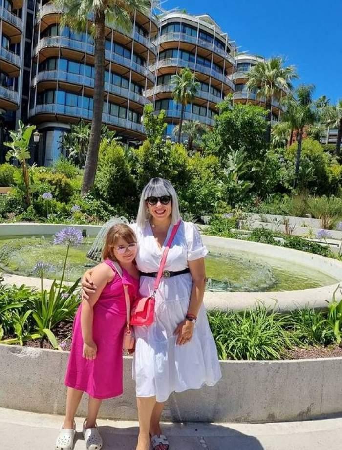 Oana Roman și fiica ei în vacanța din Franța. În spatele lor să văd mai multe clădiri, palmieri și o fântână artieziană. Cele două zâmbesc și se țin în brațe.