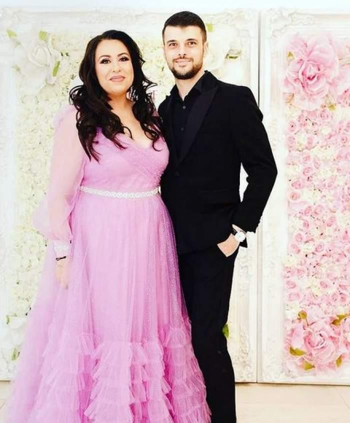 Oana Roman și Marius Elisei sunt la un eveniment. Ea poartă rochie roz, iar el costum negru și zâmbesc.