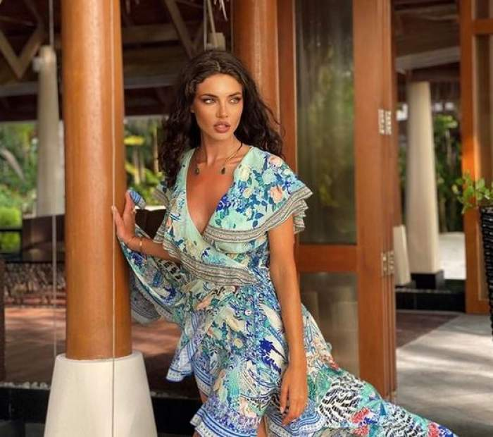 Cristina Ich e la mare și poartă o rochie bleu.