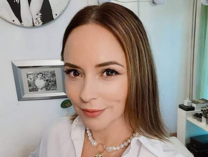 Andreea Marin își face un selfie. Vedeta zâmbește larg și poartă un colier alb și cămașă albă.