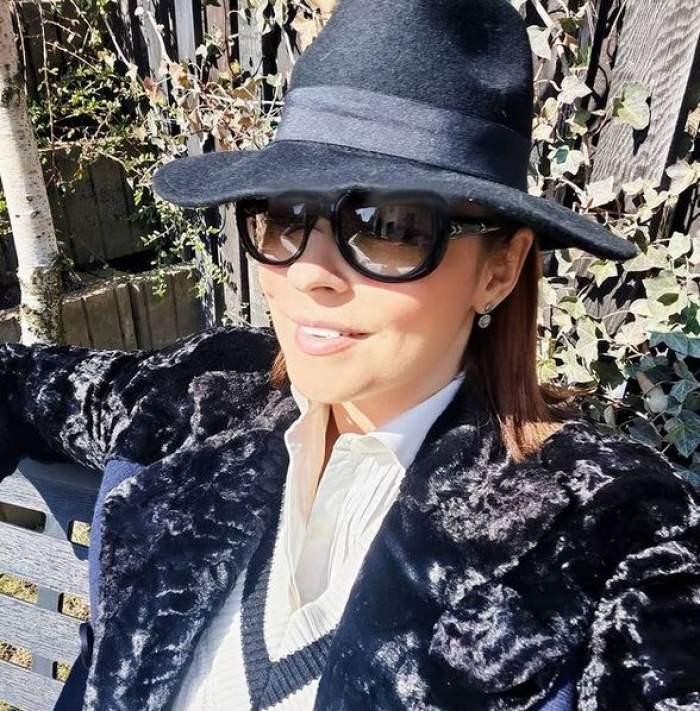 Andreea Marin poartă pălărie, ochelari de soare și haină de iarnă neagră. Vedeta zâmbește și e afară.