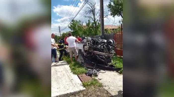 Imagine cu accidentul din județul Prahova, în care un bărbat a murit și o femeie a fost rănită. Mașina lor e răsturnată, iar lângă ea sunt mai mulți oameni.
