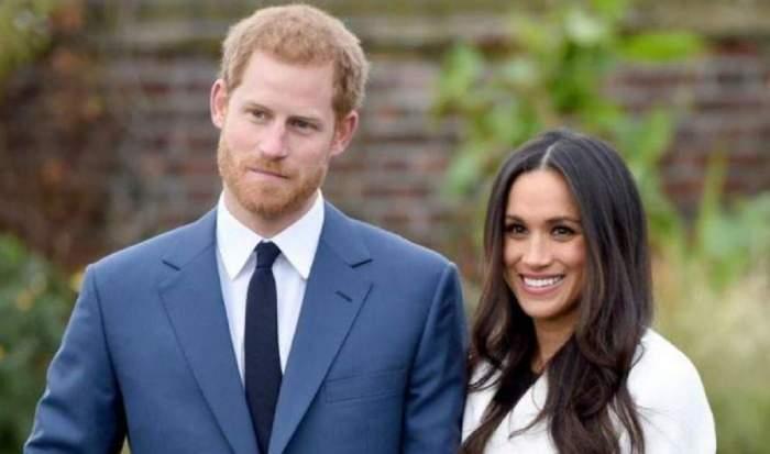 Meghan Markle și Prințul Harry se află afară. Ea poartă palton alb și zâmbește, iar el sacou albastru și cămașă albă.