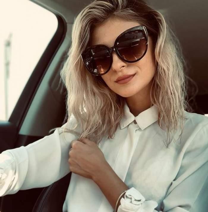 Elena Matei își face un selfie din mașină purtând ochelari de soare și cămașă albă.