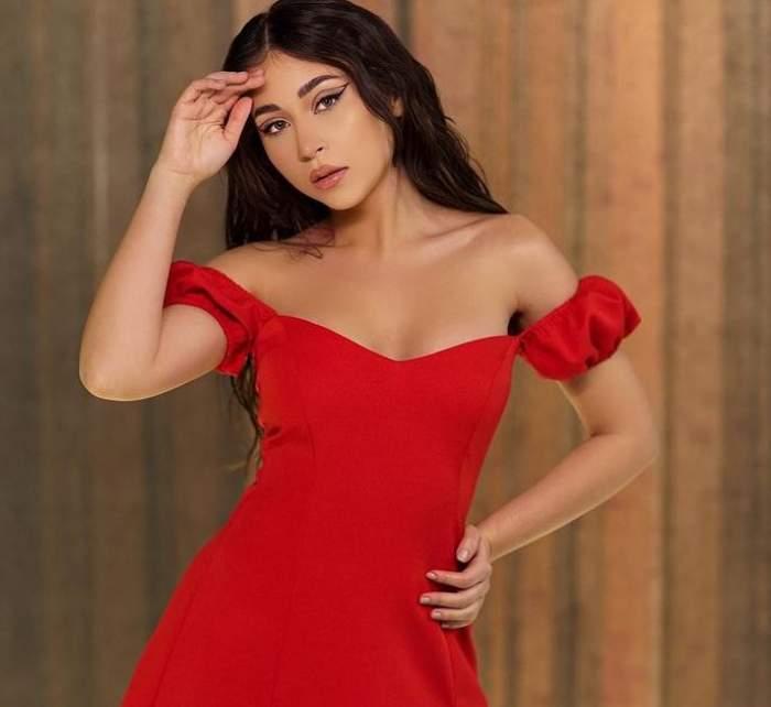 Nicole Cherry poartă o rochie roșie. Artista își ține o mână la nivelul frunții.