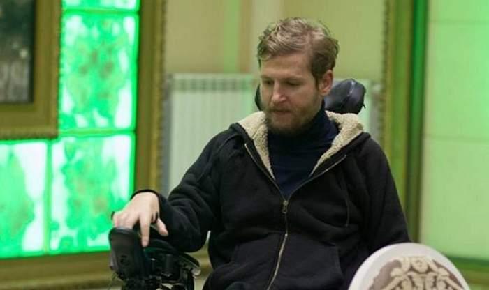 Mihai Neșu e în scaun cu rotile și poartă hanorac negru.