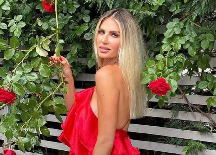 Andreea Bănică poartă o rochie roșie și zâmbește. Vedeta ține în mână tulpina unui trandafir.