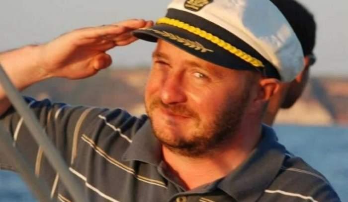 Fostul jurnalist Alin Bogdan poartă tricou gri cu dungi albe și galbene și o șapcă albă, de marinar. Acesta salută cu mâna la nivelul capului.