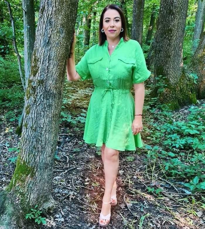 Oana Roman se ține cu o mână de un copac, în parc. Vedeta poartă rochie verde și sandale albe.