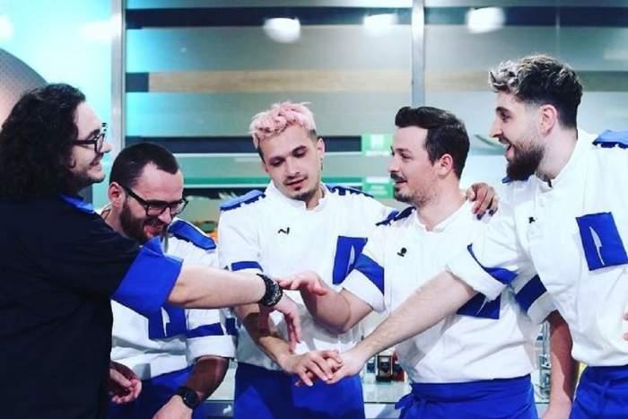 Florin Dumitrescu e în bucătăria Chefi la cuțite alături de concurenții din echipa sa, cea albastră. Toți trei zâmbesc și-și țin mâinile unul peste altul.