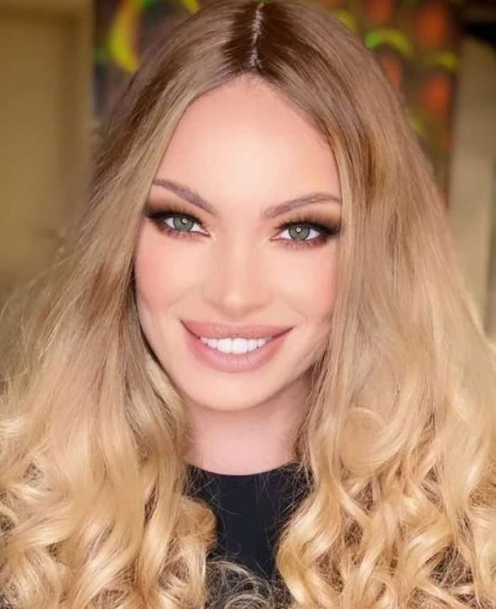 Valentina Pelinel poartă o bluză neagră și are părul aranjat în bucle. Vedeta zâmbește larg.