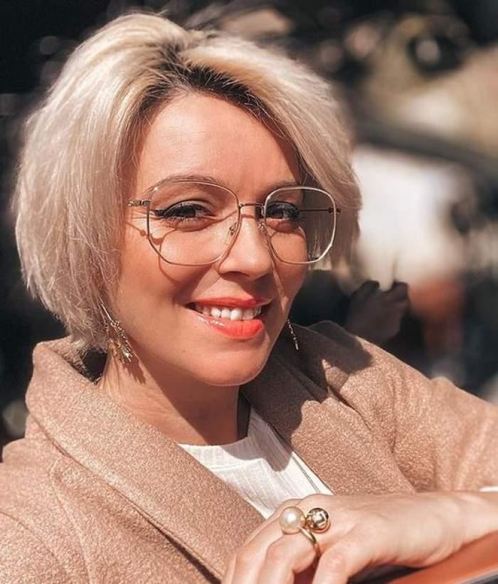 Diana Dumitrescu poartă ochelari de vedere și zâmbește.