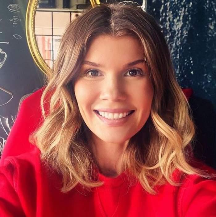 Diana Matei își face un selfie zâmbind și poartă o bluză roșie.