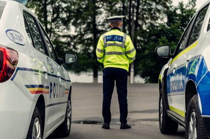 un politist între două mașini de poliție