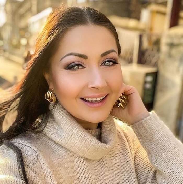 Gabriela Cristea își face un selfie. Vedeta e îmbrăcată într-un pulover crem, iar la urechi poartă niște cercei mari, aurii. Soția lui Tavi Clonda zâmbește larg.