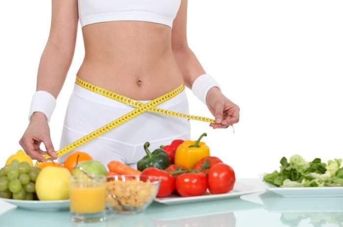 O femeie care-și măsoară talia și multe fructe și legume pe masă