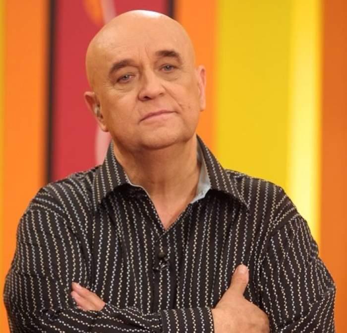Benone Sinuescu, îmbrăcat în negru, cu mâinile încrucișate
