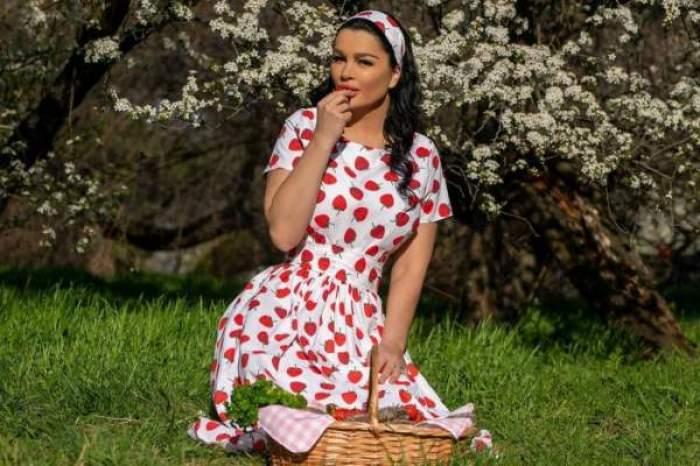Brigitte Pastramă, în rochie cu buline și un coș cu mâncare la picioare