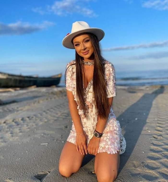Vlăduța Lupău stă în genunchi pe plajă, poartă rochie cu paiete și pălărie albă.