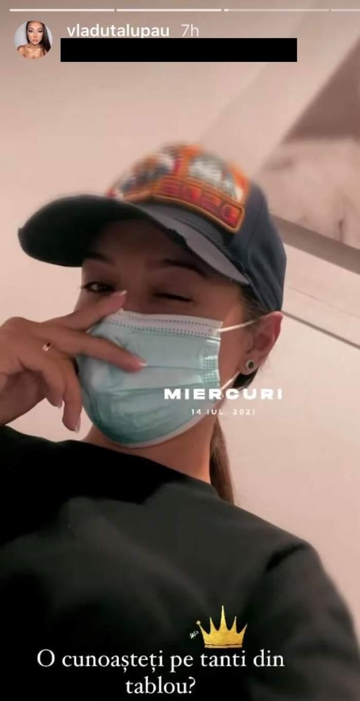 Vlăduța Lupău își face un  selfie din spital, poartă mască de protecție, tricou negru și șapcă neagră, iar în spatele ei e un tablou.