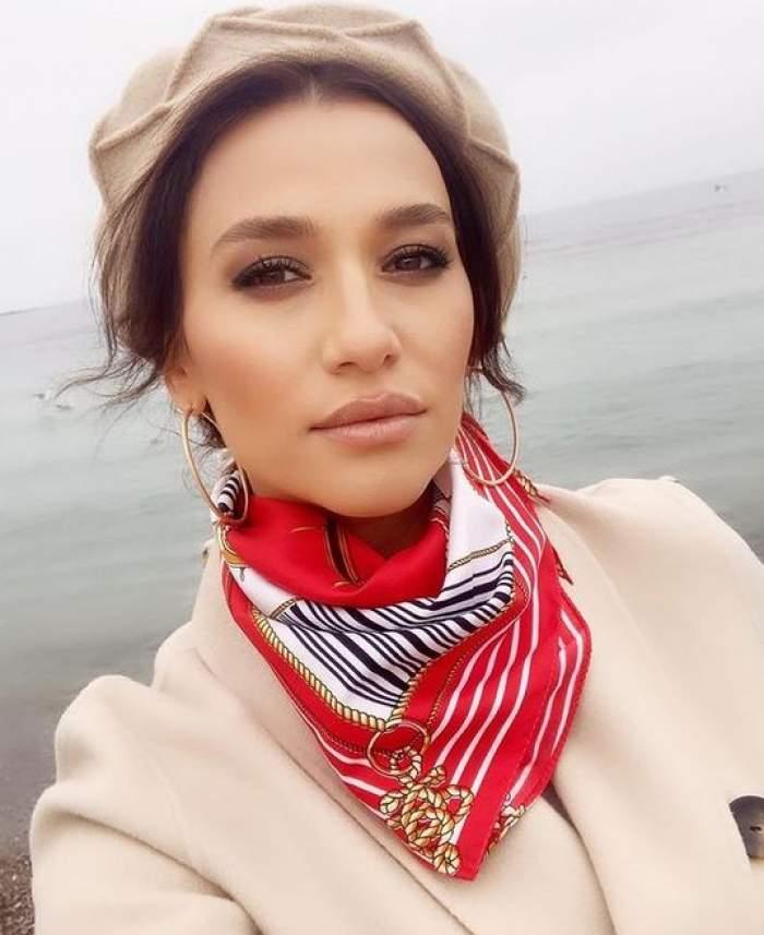 Claudia Pătrășcanu e la mare. Vedeta poartă o beretă crem pe cap. Artista e îmbrăcată cu un palton crem și are la gât o eșarfă roșie cu alb, nengru și auriu.