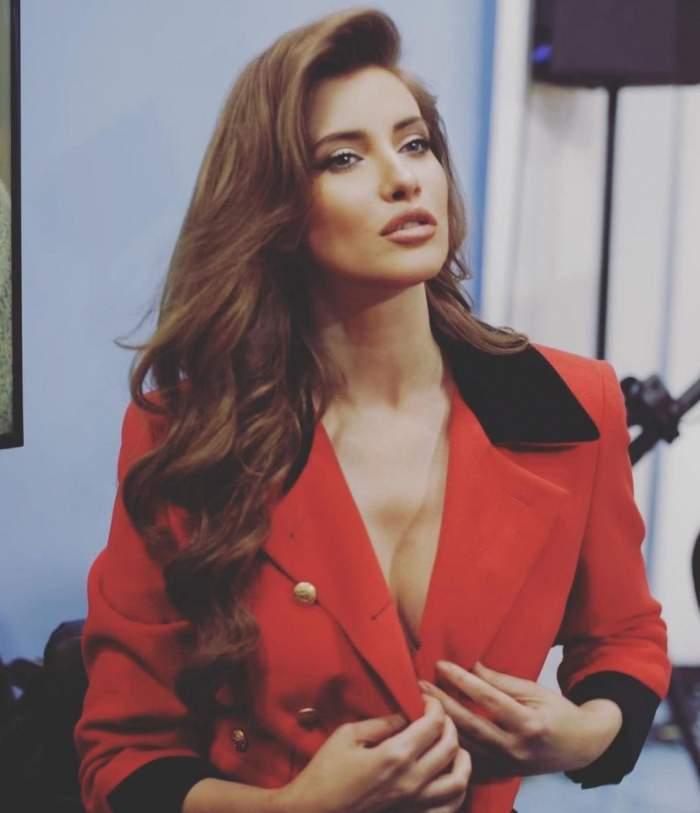 Iulia Albu, machiată, în sacou roșu, decoltat