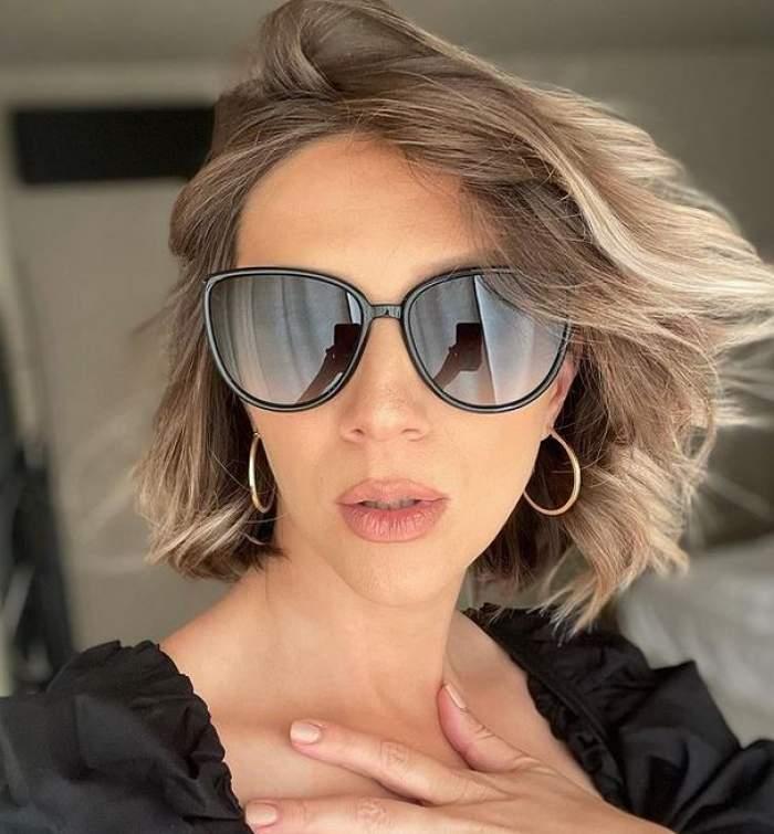 Adela Popescu poartă ochelari de soare negri și bluză neagră și își ține o mână pe piept.