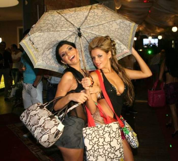 Andrea Tonciu și Sânziana Buruiană, îmbrăcate sumar, cu o umbrelă în mână