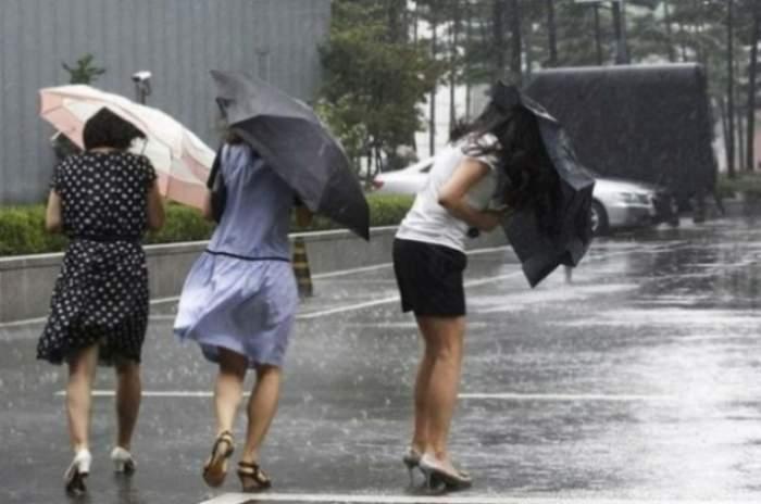 Mai multe femei, cu umbrele, pe o stradă ploioasă