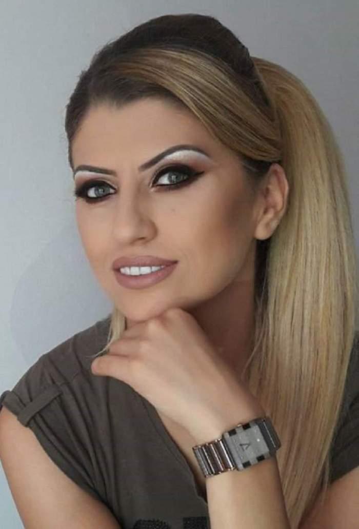 Alina Radi, cu mâna la barbă, zâmbitoare, în ținută închisă la culoare
