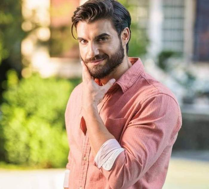 Andi Constantin, cu mâna la față, în cămașă roz