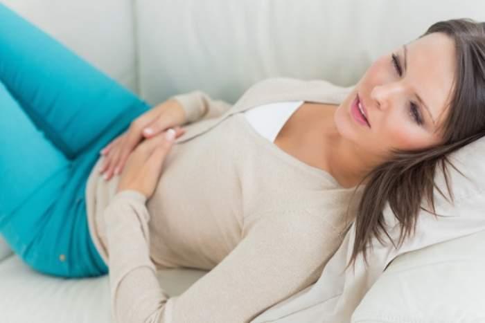 O femeie care stă pe pât cu mâinile pe abdomen