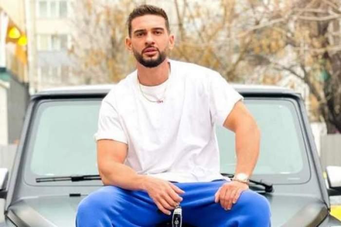 Dorian Popa, în alb și albastru, stă pe mașină