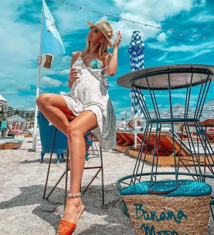 Gabriela Prisăcariu e la mare și stă pe scaun. Vedeta poartă pălărie de paie, rochie albă pe deasupra unui costum de baie albastru, are papuci oranj în picioare și ține în mână un pahar.