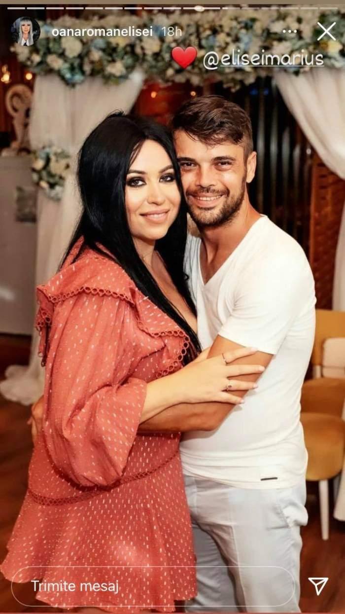 Oana Roman și Marius Elisei stau îmbrățișați la un eveniment și zâmbesc. Ea poartă rochie maro, iar el e îmbrăcat în alb.
