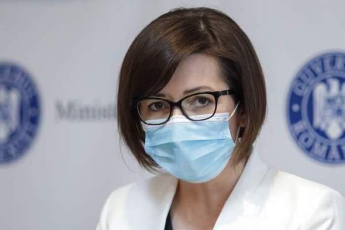 Oana Mihăilă, îmbrăcaă în alb, cu ochelari și mască de protecție pe față