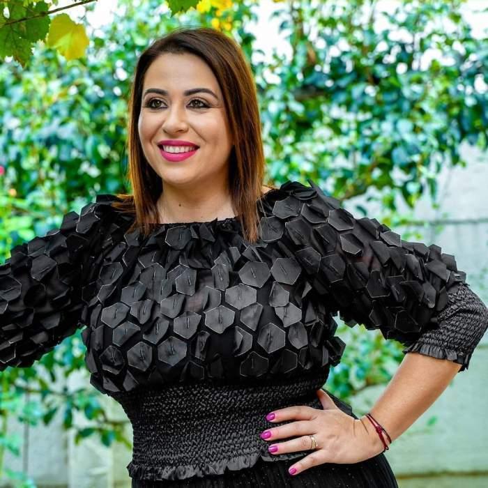 Oana Roman, zâmbitoare, în rochie neagră