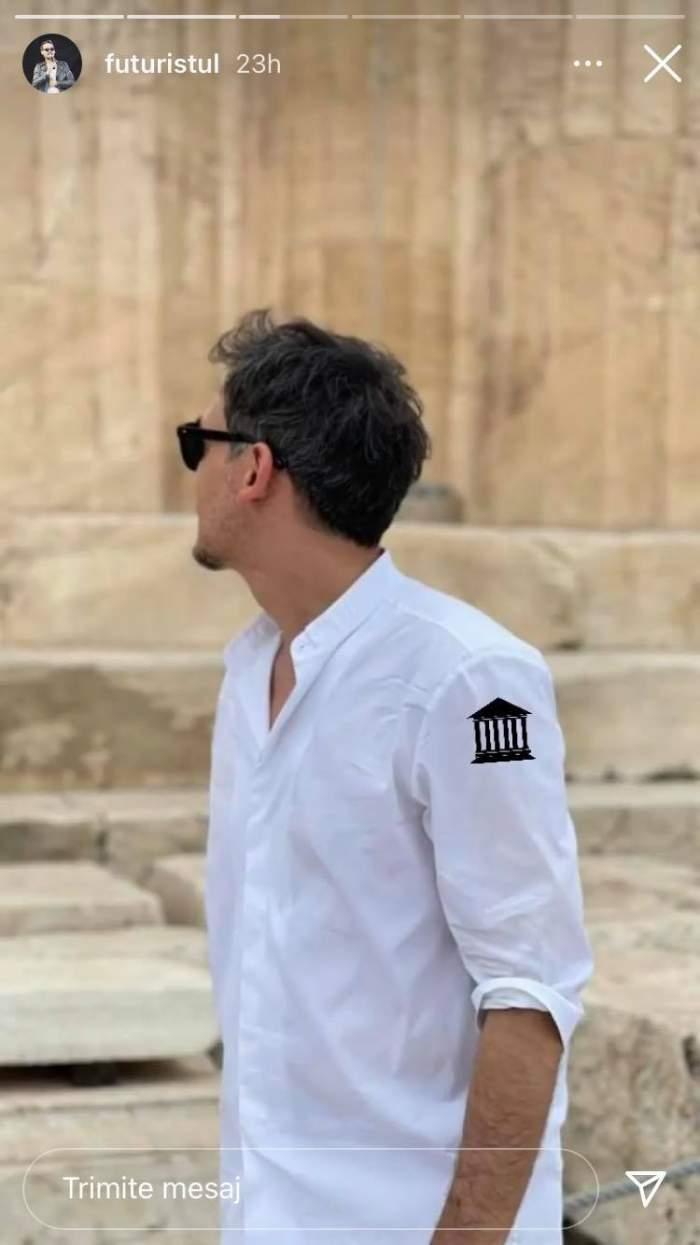Răzvan Simion e în Grecia, poartă ochelari de soare negri și cămașă albă și privește într-o parte.