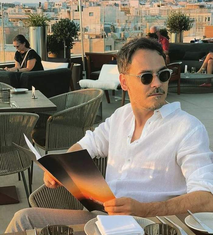 Răzvan Simion stă la terasă în Grecia, are meniul în mână și poartă ochelari de soare și cămașă albă.