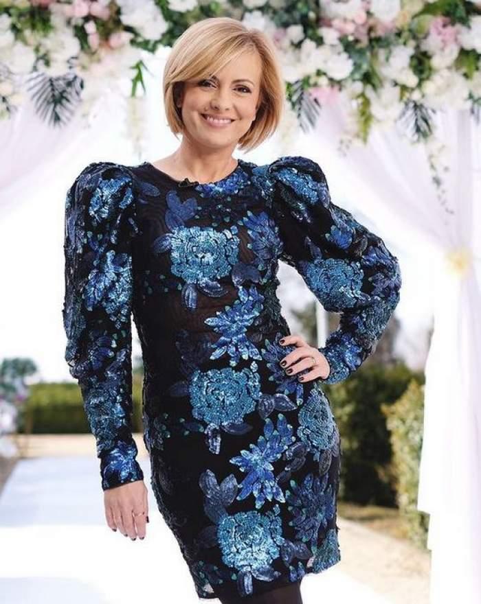 Simona Gherghe zâmbește larg, poartă o rochie neagră cu flori albastre și ține o mână în șold.