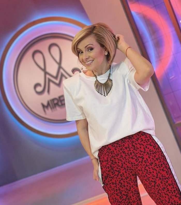 """Simona Gherghe poartă un tricou alb și o pereche de pantaloni roșii cu animal print. Vedeta este în platoul emisiunii """"Mireasa""""."""