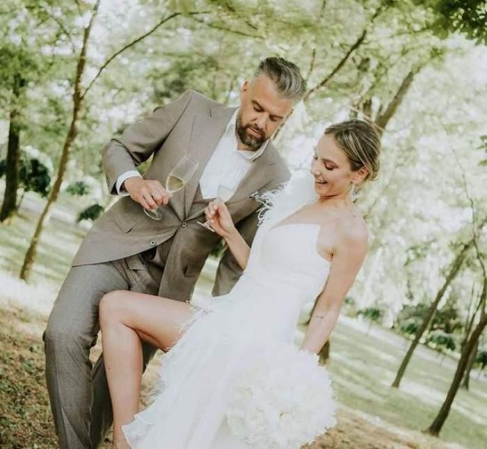 Roxana Ionescu și Tinu Vidaicu sunt la nuntă. Ea poartă o rochie albă de mireasă, iar el un costum gri și țin paharele în mâini.