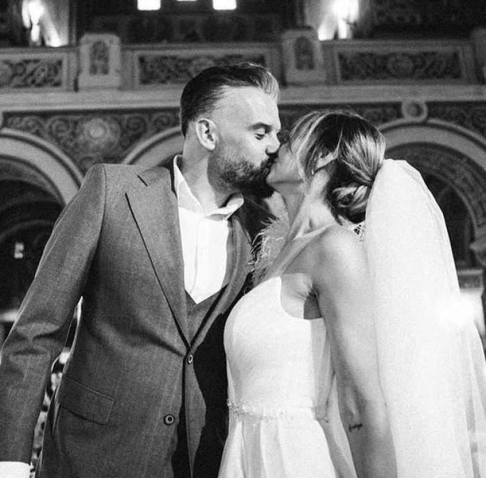 O poză alb-negru cu Roxana Ionescu și soțul ei la cununia religioasă. Cei doi se sărută. Ea poartă rochie de mireasă, el costum.